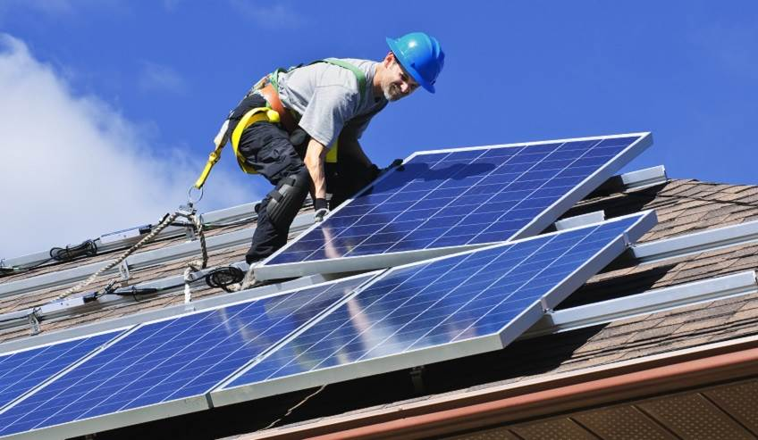Man on a roof installing solar panels.