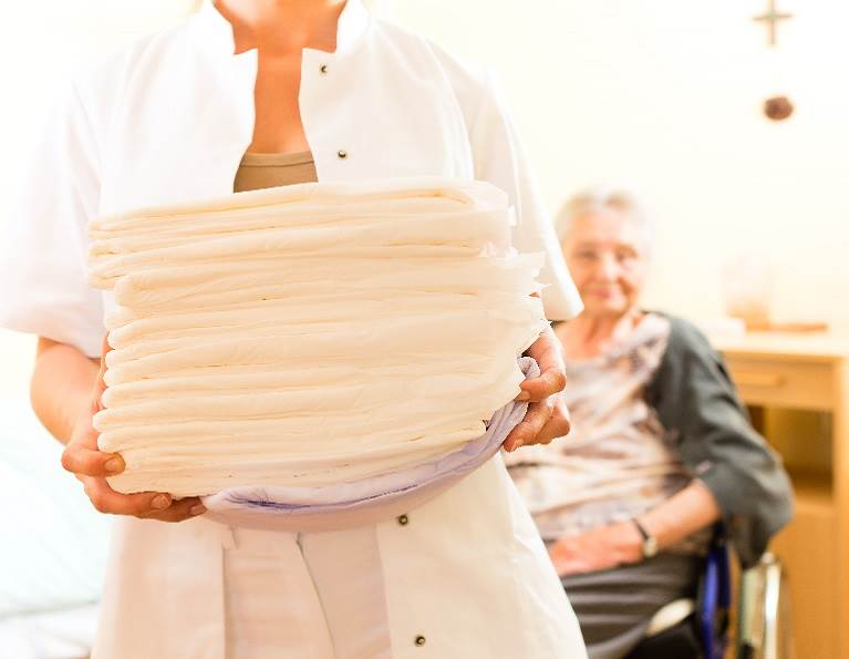 Nurse carrying a stack of clean medical pads with ODOGard odor eliminating technology.