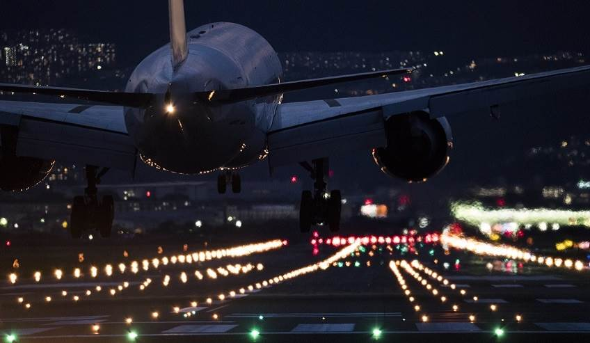 Airplane landing at night with the guidance of runway lights.