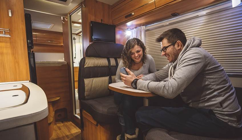Couple inside an RV showing wood panels for the transportation market.